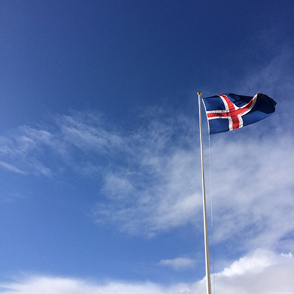 The flag of Iceland fluttering in a blue sky near Budir, Iceland | meljoulwan.com